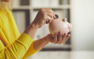 Frau steckt Geld in ein Sparschwein