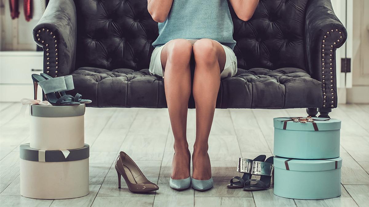 Vermögensaufbau Frau sitzt auf einem Sofa vor einer Auswahl an Schuhen